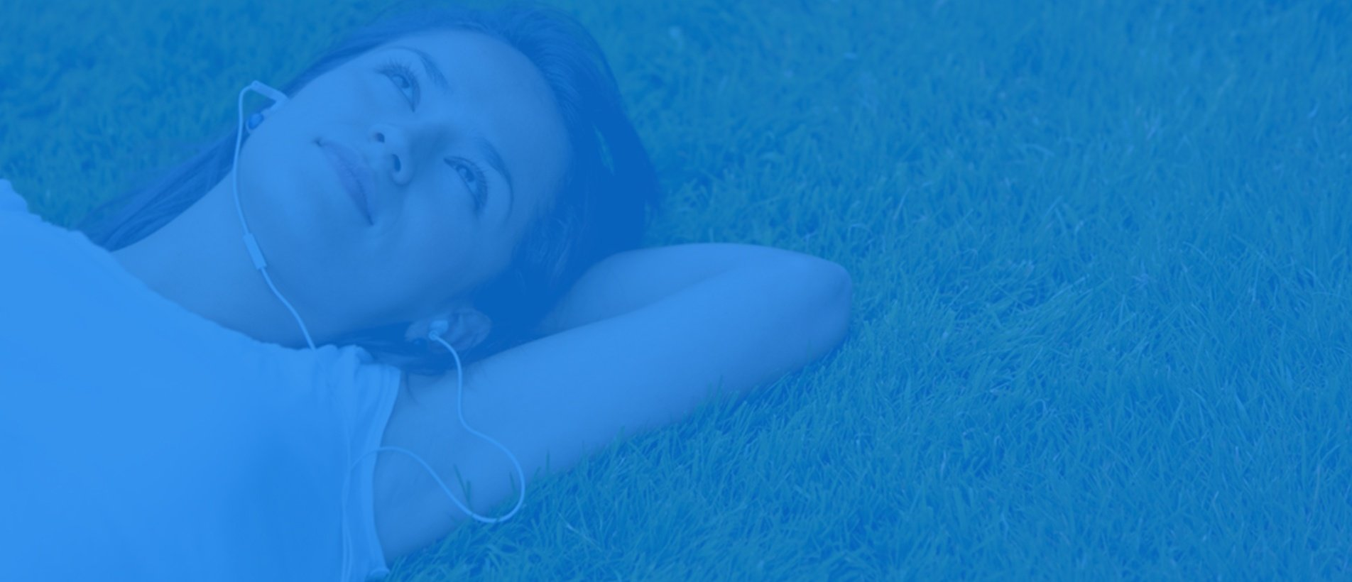 Pensive woman lying on grass listening to music outdoors.jpeg